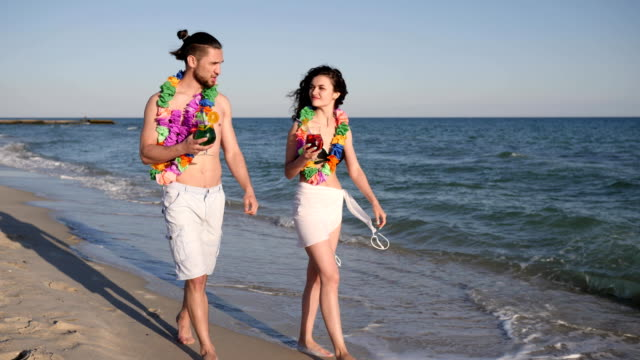 walking barefoot on sand beach, couple in love drink colored cocktails, Hawaii romantic trip, happiness people walk at resort video