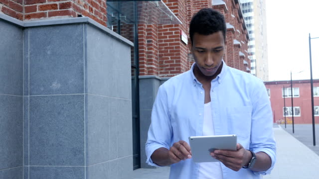 Walking Black Man and Using Tablet for Browsing video