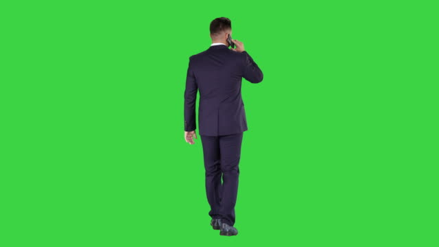 walking business man with talking on mobile phone on a green screen, chroma key - точка съёмки стоковые видео и кадры b-roll