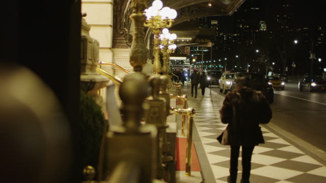 walking by a building with golden ornaments at night - ludzka osada filmów i materiałów b-roll