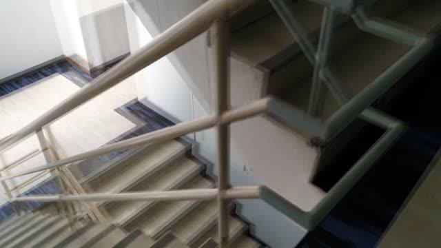 vídeos de stock e filmes b-roll de walking down fire escape - concrete wall interior