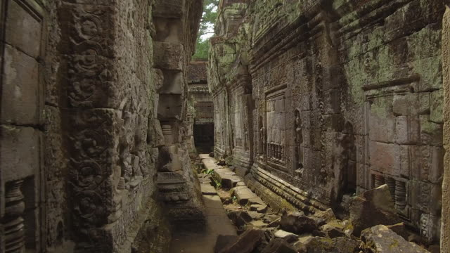 pov: walking down narrow path between two beautiful decaying buddhist temples. - tempio video stock e b–roll