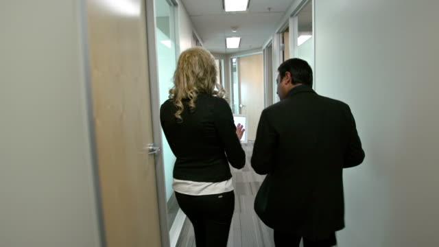 vídeos y material grabado en eventos de stock de a pasos de la oficina corredor para una reunión. - stabilized shot
