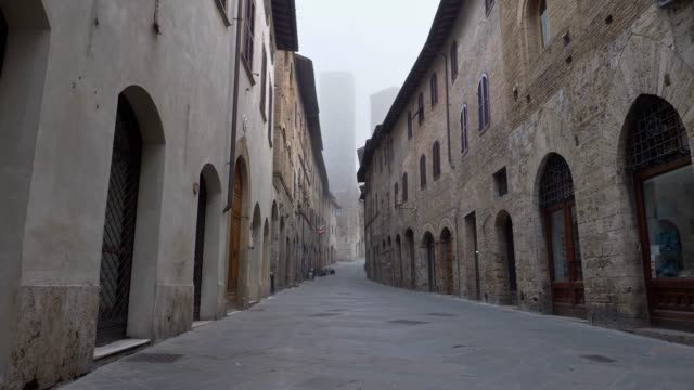 Walking down the street of San Gimignano medieval town early in the morning. Tuscany, Italy.