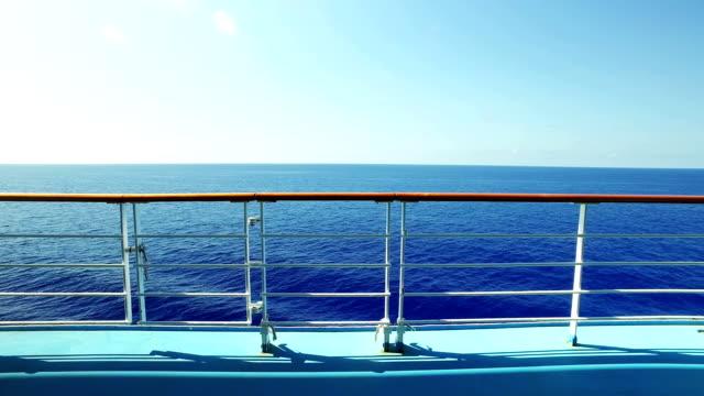 walking establishing shot looking over cruise ship railing at ocean - parapetto barriera video stock e b–roll