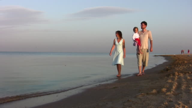 walking family with girl on beach video