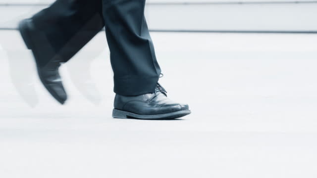 Walking. Fast pace and slow in the city. Mixed group of people walking in the city, lower body, some smart shoes some casual. The middle section is a man wearing office shoes, he is closed down but the beginning and end is faster in realtime. dress shoe stock videos & royalty-free footage