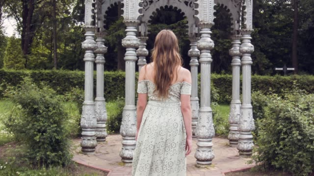 Walking girl in beautiful elegant dress with flowing hair with view from the back Young girl strolls through fairytale forest park with arches and columns. young woman walking away along nature path. Walking girl in beautiful elegant dress with flowing hair with view from the back princess stock videos & royalty-free footage