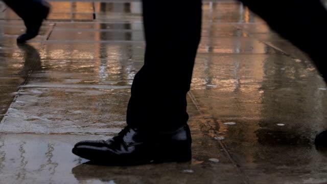 walking in the rain. city commuter's feet. - inghilterra sud orientale video stock e b–roll