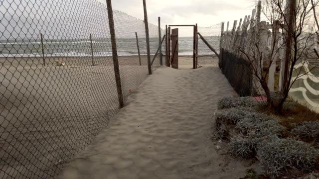 海と曇りの空に向かって開くフェンスと砂の道で日没に海に向かって風を歩いて - 叙情的な内容点の映像素材/bロール