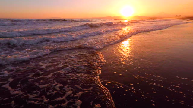 Walking in to the sea at sunset -4K video