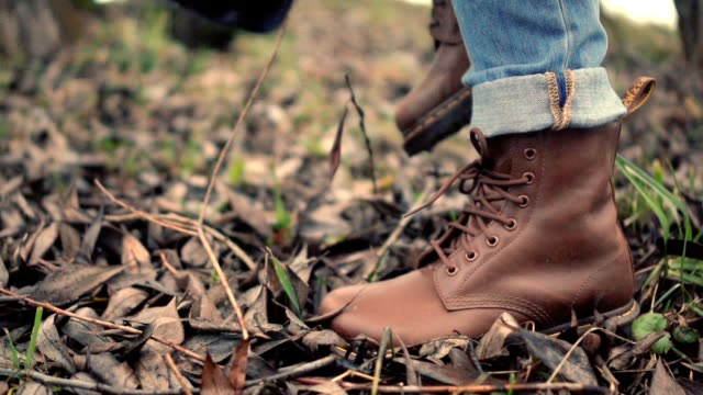 walking legs in brown shoes side view. walking feet in brown leather boots - fare un passo video stock e b–roll