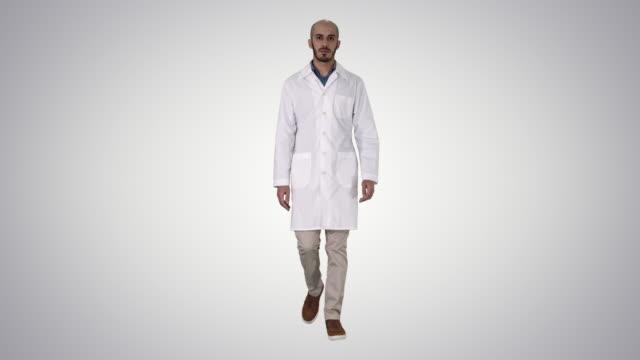 walking manlig arabisk läkare på gradient bakgrund - hospital studio bildbanksvideor och videomaterial från bakom kulisserna