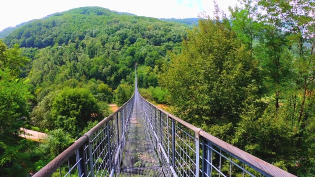 Walking on a suspension bridge over a creek and a forest . Tuscany, Italy