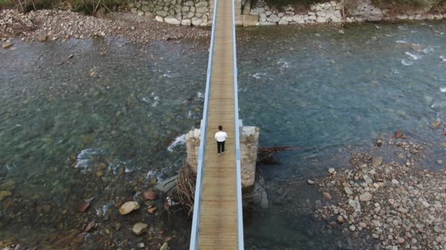 Walking on a wooden pedestrian bridge over a river