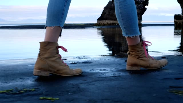 stockvideo's en b-roll-footage met wandelen op zwart zand. close-up op schoenen - geologie