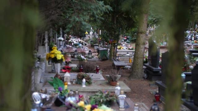 walking på kyrkogården mellan gravestones korsar och träd - ljus på grav bildbanksvideor och videomaterial från bakom kulisserna