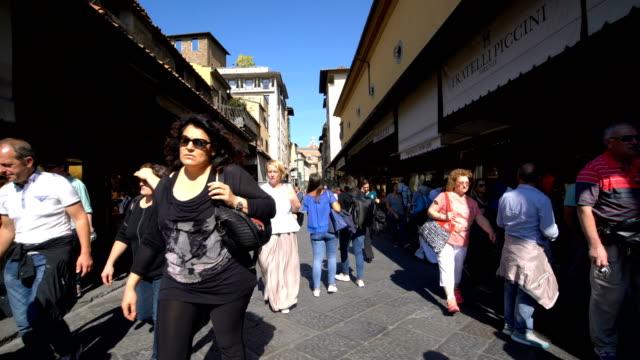 Caminar sobre el puente de Ponte Vecchio en Florencia, Italia - vídeo