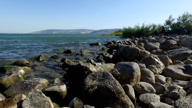 Walking on Rocky Shoreline at Sea of Galilee video