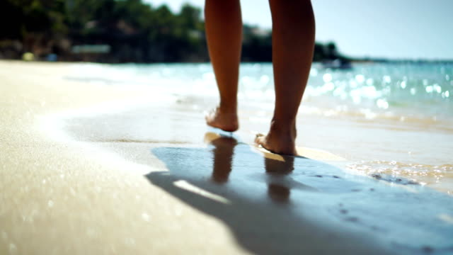 Walking on the sandy beach Close-up video of woman legs walking on the beach in shallow water. holiday stock videos & royalty-free footage