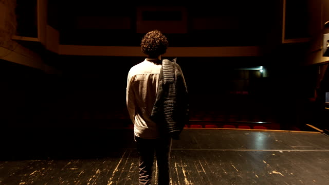 Walking on the theater stage There is one young man, age 23. He is in theater and he have a rehearsal. He is an actor, he have a curly hair. performer stock videos & royalty-free footage