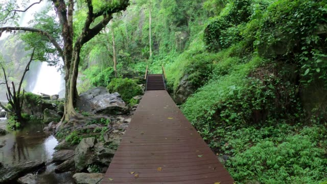 Walking on wooden bridge over a river in the Khlong lan waterfall