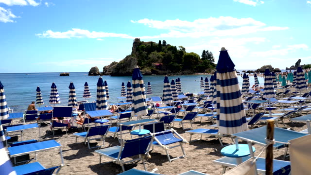 Walking Past Rows of Umbrellas in front Beachside Paradise, Isola Bella