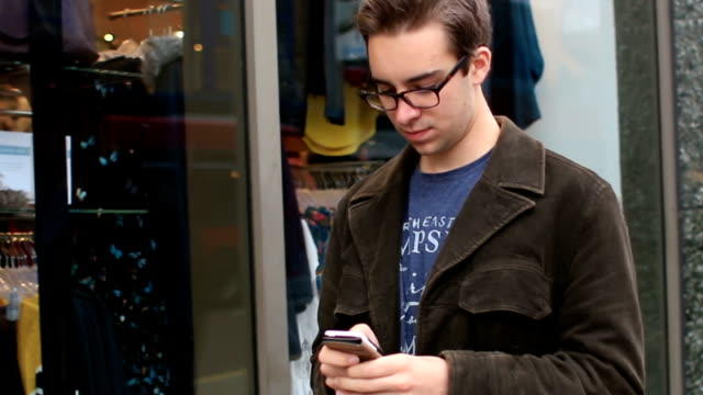 Walking past shops using a smartphone. video