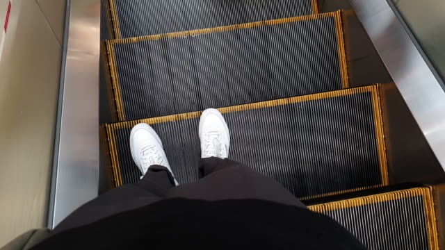 4k walking standpunkt . füße bewegen sich nach unten und steigen aus rolltreppe - rolltreppe stock-videos und b-roll-filmmaterial