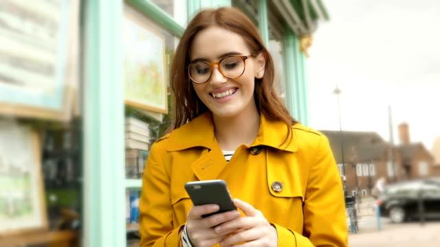walking leende läsa telefonmeddelande. ung kvinna klädd i regnrock. - telefonmeddelande bildbanksvideor och videomaterial från bakom kulisserna