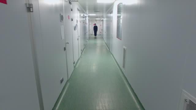 Walking through laboratory corridor. Female worker going chemical lab corridor video