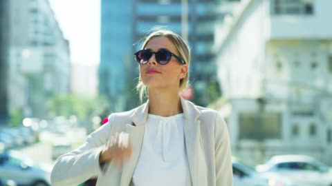 Walking through the city with style 4k video footage of an attractive young businesswoman walking through the city alone and putting her sunglasses on fashionable stock videos & royalty-free footage