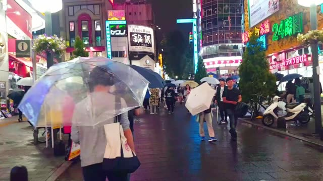 Walking Time lapse crowd people walking and crossing road in the city while raining