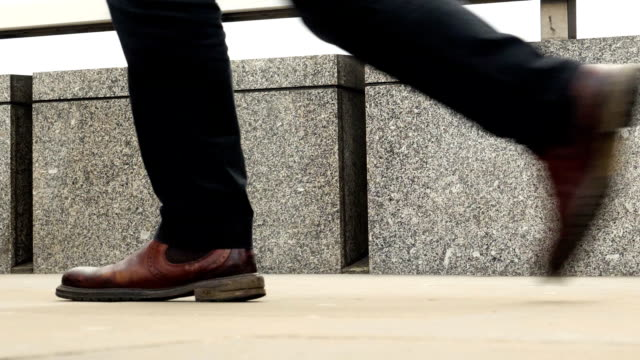 walking to work. commuters legs and feet low angle side view. - london bridge inghilterra video stock e b–roll