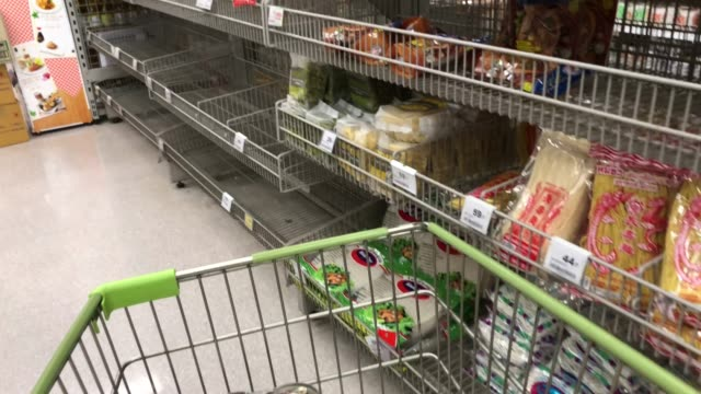 walking with shopping cart in supermarket , empty shelf with out product , crisis from COVID-19 fever