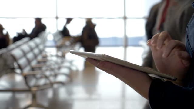 Walking with tablet computer in airport lounge video