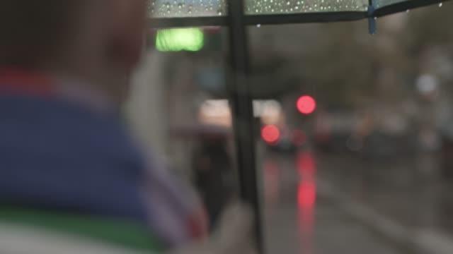 camminare con l'ombrello sotto la pioggia - dorso umano video stock e b–roll