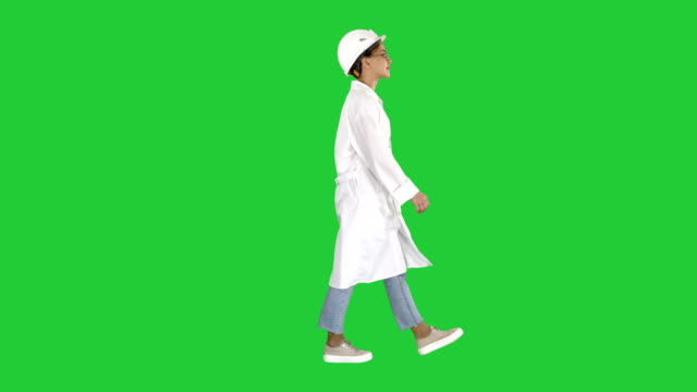 vidéos et rushes de ingénieur de femme marche avec mains dans les poches sur un écran vert, chroma key - uniforme