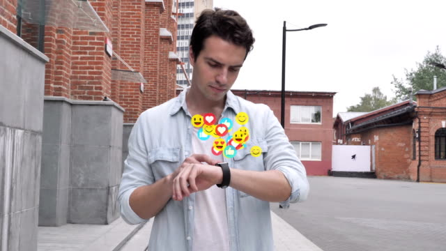 Walking Young Man Using Smartwatch,  Flying Smileys, Emojis and Likes