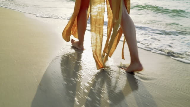 TRACKING SHOT: Walking young woman's feet on the beach Tracking shot of walking young woman's feet on the beach. coastal feature stock videos & royalty-free footage