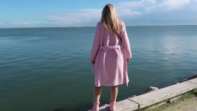 Walks in the fresh air. Blonde woman tourist in a pink coat and boots walking along the sea on the promenade enjoying the Sunny weather. Lisbon, Portugal.