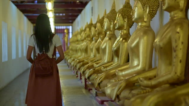 Walks praying Woman traveller walks with pay gentle respect to the buddha statue in the temple, praying respect for a better life forward, buddhist new year festival of Songkarn day sukhothai stock videos & royalty-free footage