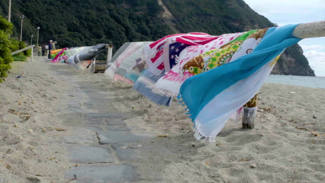 Walkway along wooden guard rails on beach with swaying beach towels hung over