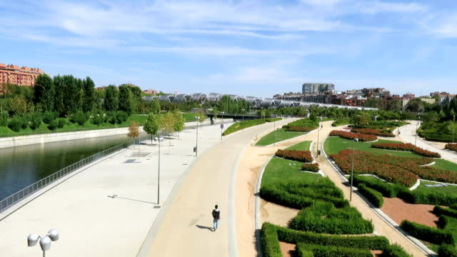 walkway in Madrid river landmark cityscape of walkway runway garden park with star shape flowers green lawn grass and modern metal bridge in Madrid city Spain Europe hd format stock videos & royalty-free footage