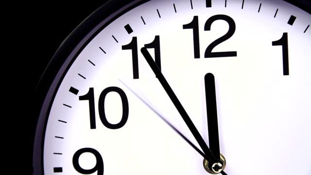 vídeos de stock e filmes b-roll de relógio de parede em um preto 23:55 close-up - 20 24 anos