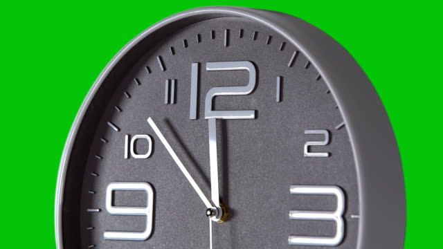 Wall clock on a green background. Time lapse Round gray wall clock on a green background. Time laps. 12:00 wall clock stock videos & royalty-free footage