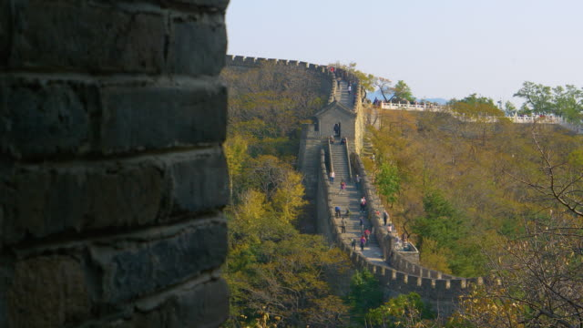 CLOSE UP: Wall creates a window offering a view of tourists exploring Great Wall