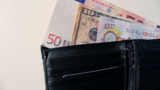 wallet of different currencies - pound sterling isolated bildbanksvideor och videomaterial från bakom kulisserna