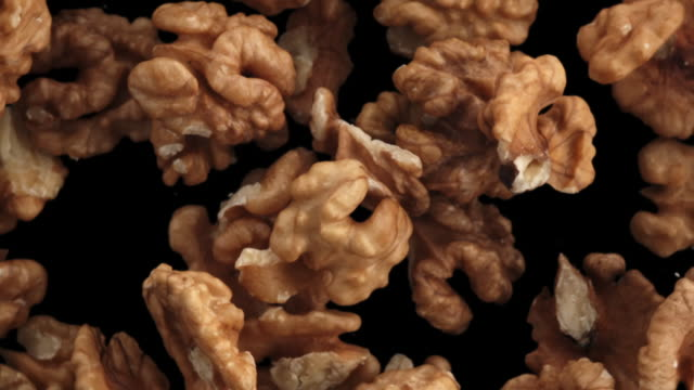 walnuts in the air on black background - noci video stock e b–roll