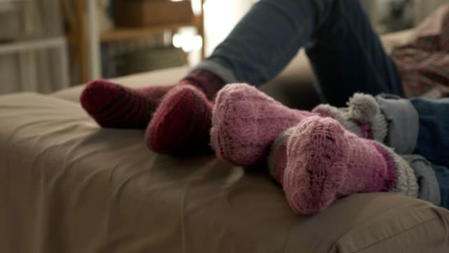 Wan's pair of legs lies on the couch in woolen socks, near plan, comfort. 60 fps Wan's pair of legs lies on the couch in woolen socks, near plan, comfort. 60 fps 4k sock stock videos & royalty-free footage